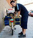 Brevbärare som ser glad ut över att få dela ut post i stan. Foto: Posten