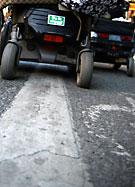 Bakhjulen p en elrullstol rullar fram över våt asfalt