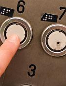 Några knappar i en hiss och en hand vars innehavare väljer och vrakar mellan utbudet av våningsplan.