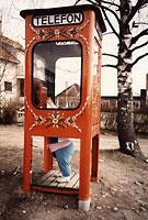 Gammal telefonkiosk där en kortvuxen person försöker nå luren.