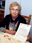 Vivian Behm håller upp ett brev från funktionshinderörelsen