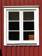 Spröjsat fönster med vitt foder i röd stuga
