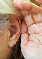 Hand kupad bakom örat.
