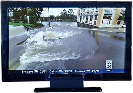 En TV visar bilder från översvämningen i Australien tidigare i år.