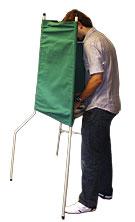 Man lägger sin röst bakom en grön valskärm avsedd för stående personer.
