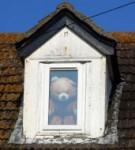 Litet vindsfönster med en nallebjörn innanför