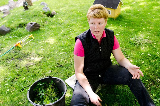 Nathalie Nordlund sitter på gräset och rensar ogräs