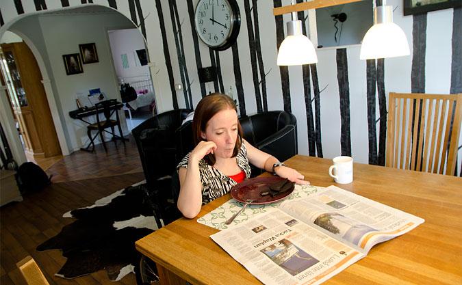 Malin Lundström sitter vid matbordet och läser en tidning