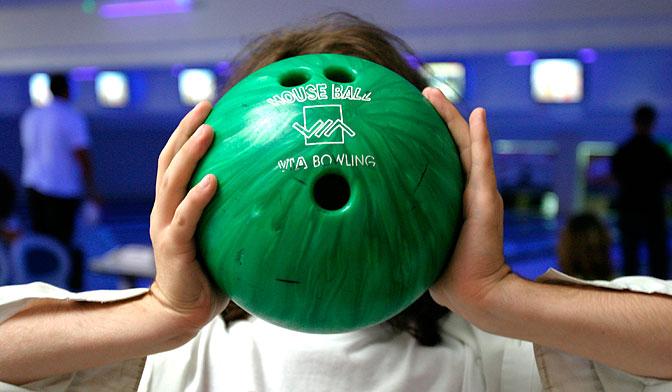 En person håller ett bowlingklot framför ansiktet