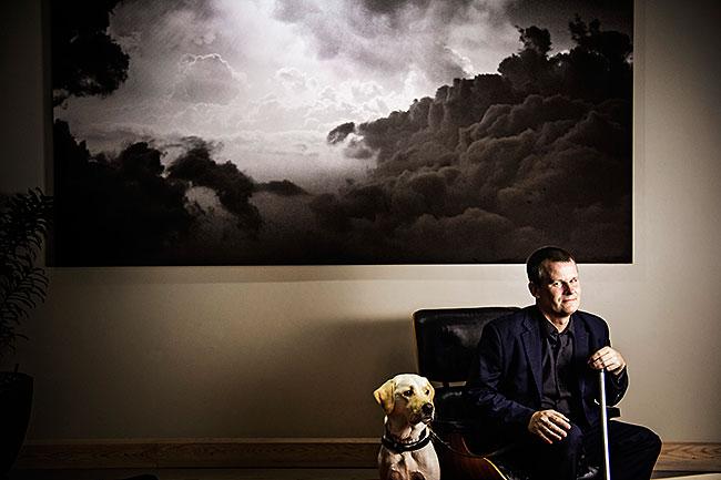 Magnus Berglund sitter i en fåtölj med en stor tavla med moln på bakom sig.